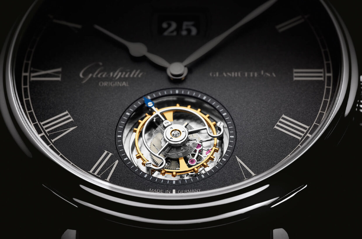 Visible whirlwind Flying Tourbillon on dial side, blued steel tip of tourbillon cage serves as seconds hand, positioning at 6 o'clock as visual counterpoint to Panorama Date at 12 o'clock