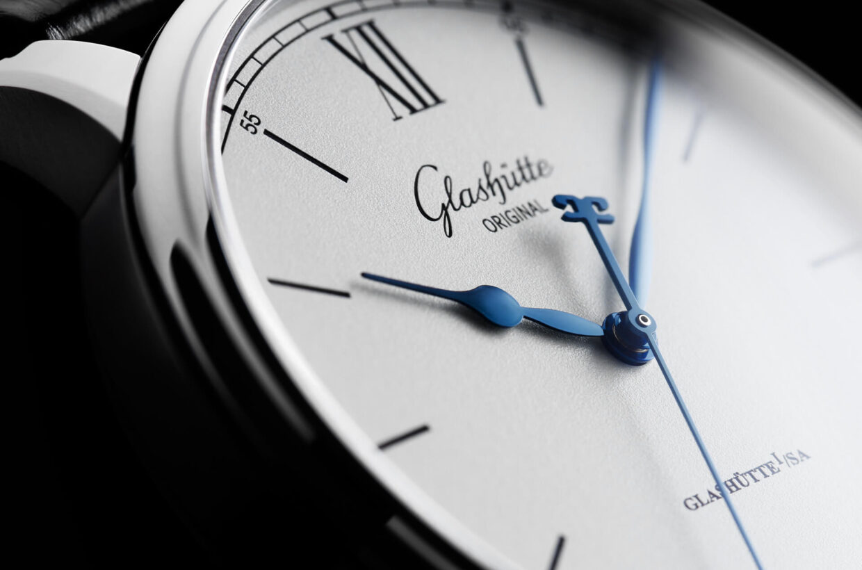 Silver-coloured dial Dial with silver-coloured grainé lacquer, laser engraved and galvanised black railroad chapter ring, Roman numerals and indexes, polished and blued hands
