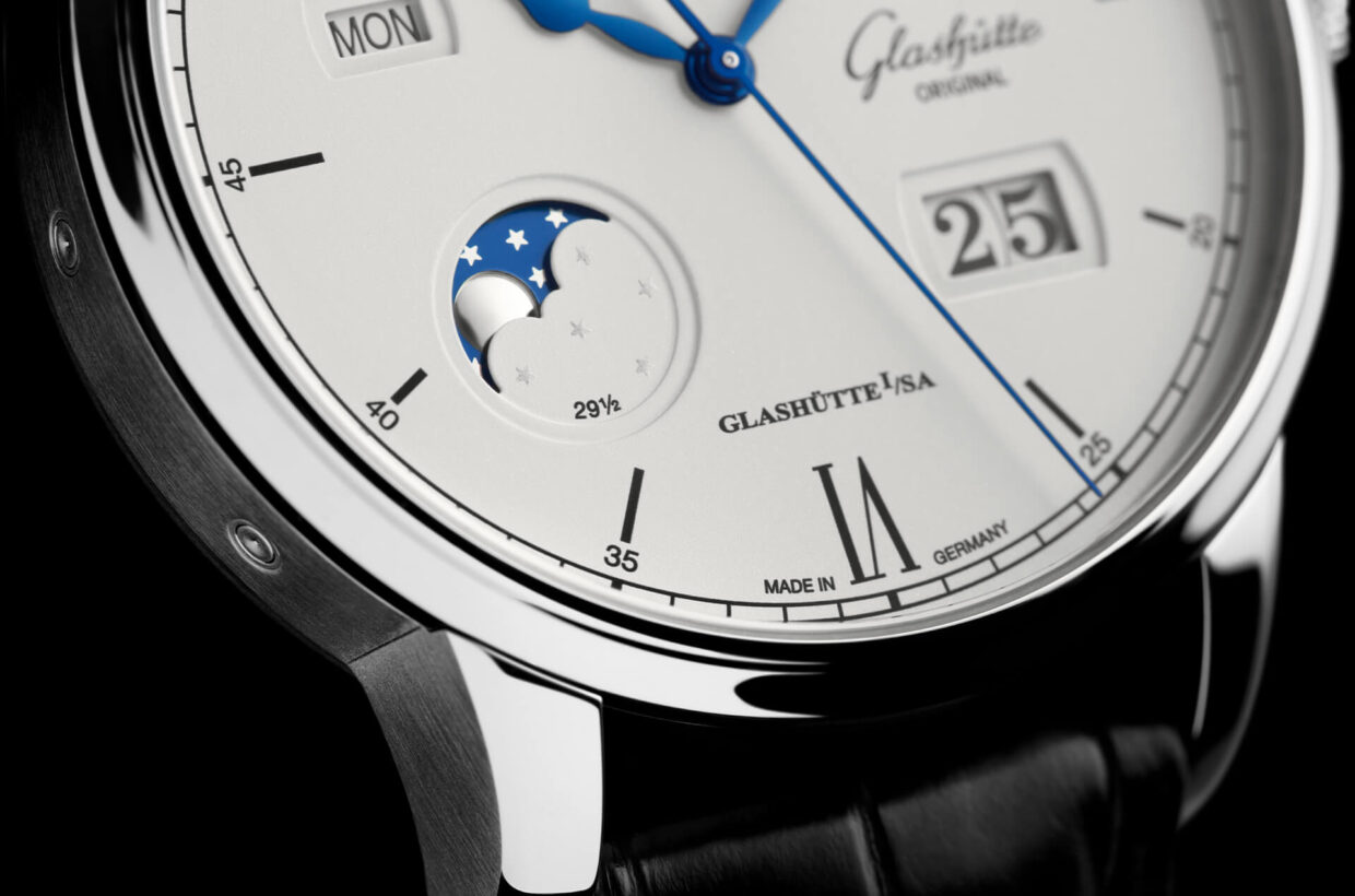 Moon phase in silver and blue Elaborate moon phase design takes up cool hue of stainless steel case, domed silver-coloured moon set against galvanic blue sky with silver-coloured stars