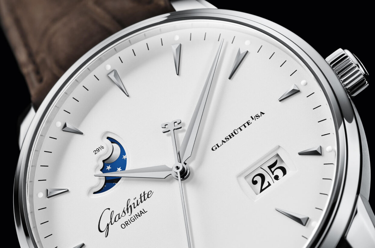 White dial White varnished dial with matt surface, appliques in white gold, sword-shaped hands, Panorama Date with black numerals on white background, moon phase display with silver-coloured moon and blue starry sky